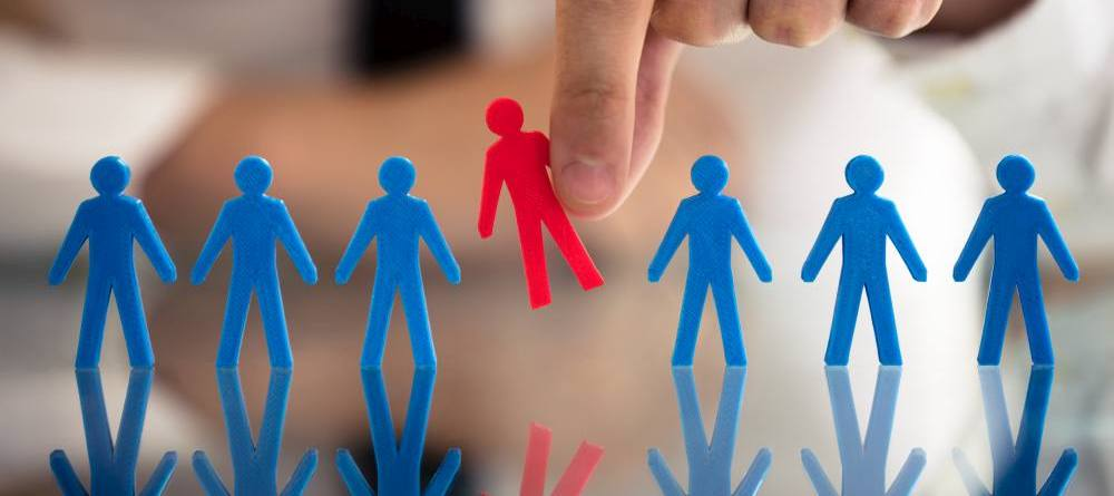 Businessperson's Hand Picking Red Human Figures Amongst Blue Figures In A Row